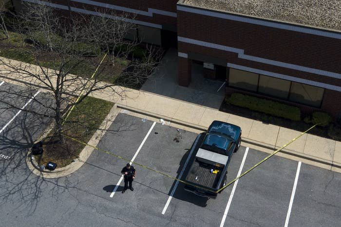 An aerial shot shows a cop standing near a taped-off area at the scene of a shooting