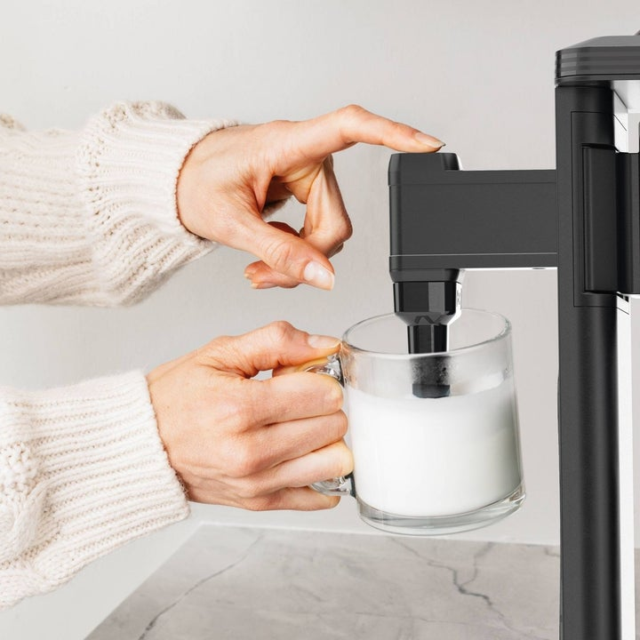 Person foaming their milk with the coffee maker