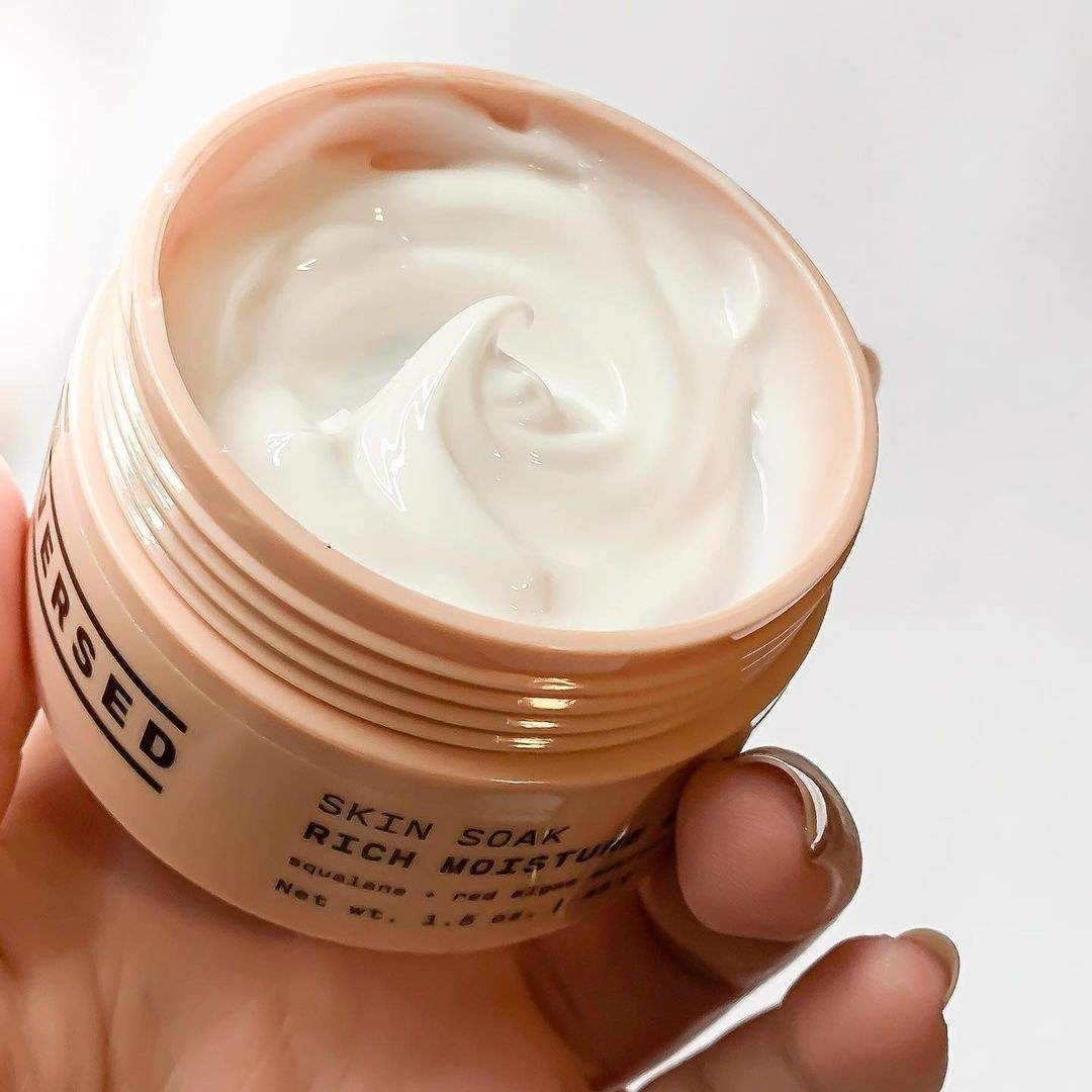 Hand holding open jar of Versed Skin Soak cream
