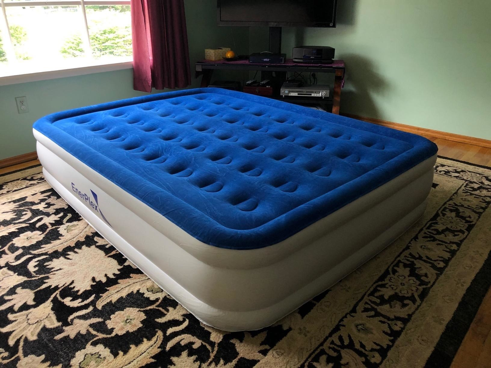 Reviewer showing blue flock-topped air mattress with never-leak technology