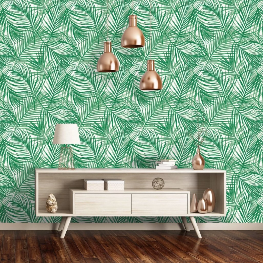 The wallpaper which is green and has tropical leaf patterns