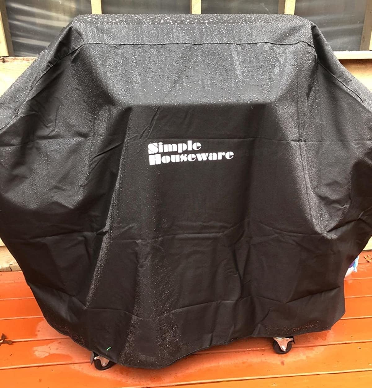 Reviewer using product to protect grill from rainy weather