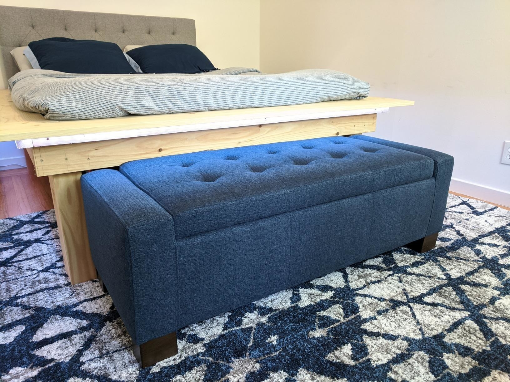 reviewer image of the tufted fabric midnight blue ottoman at the foot of a wooden bed