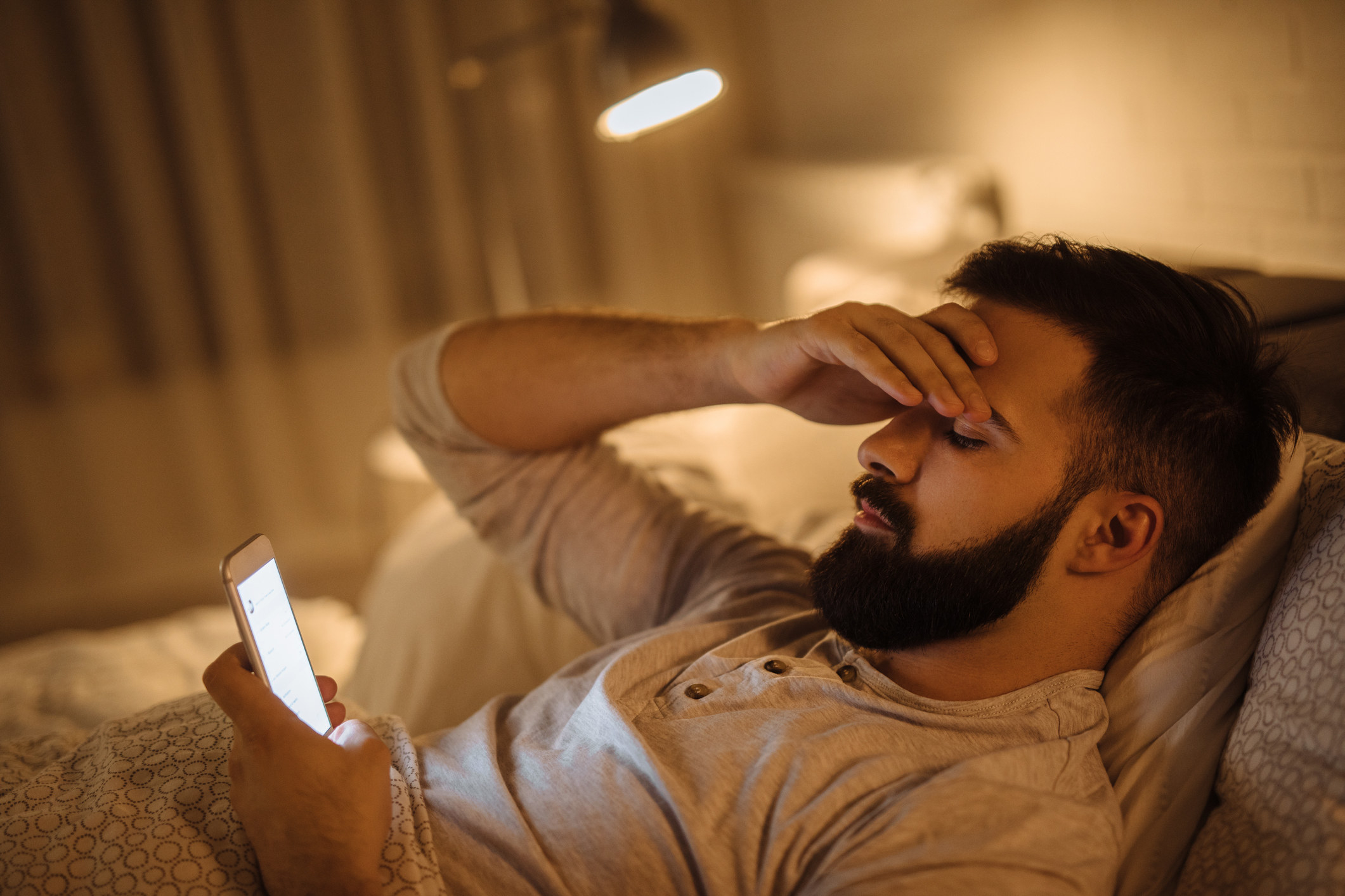 A stressed out man reading a text on his phone