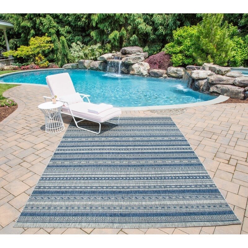 blue and white striped rug outdoor under a lounge chair and next to a swimming pool