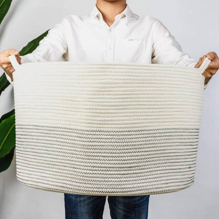 A person holding up an oversized rope basket