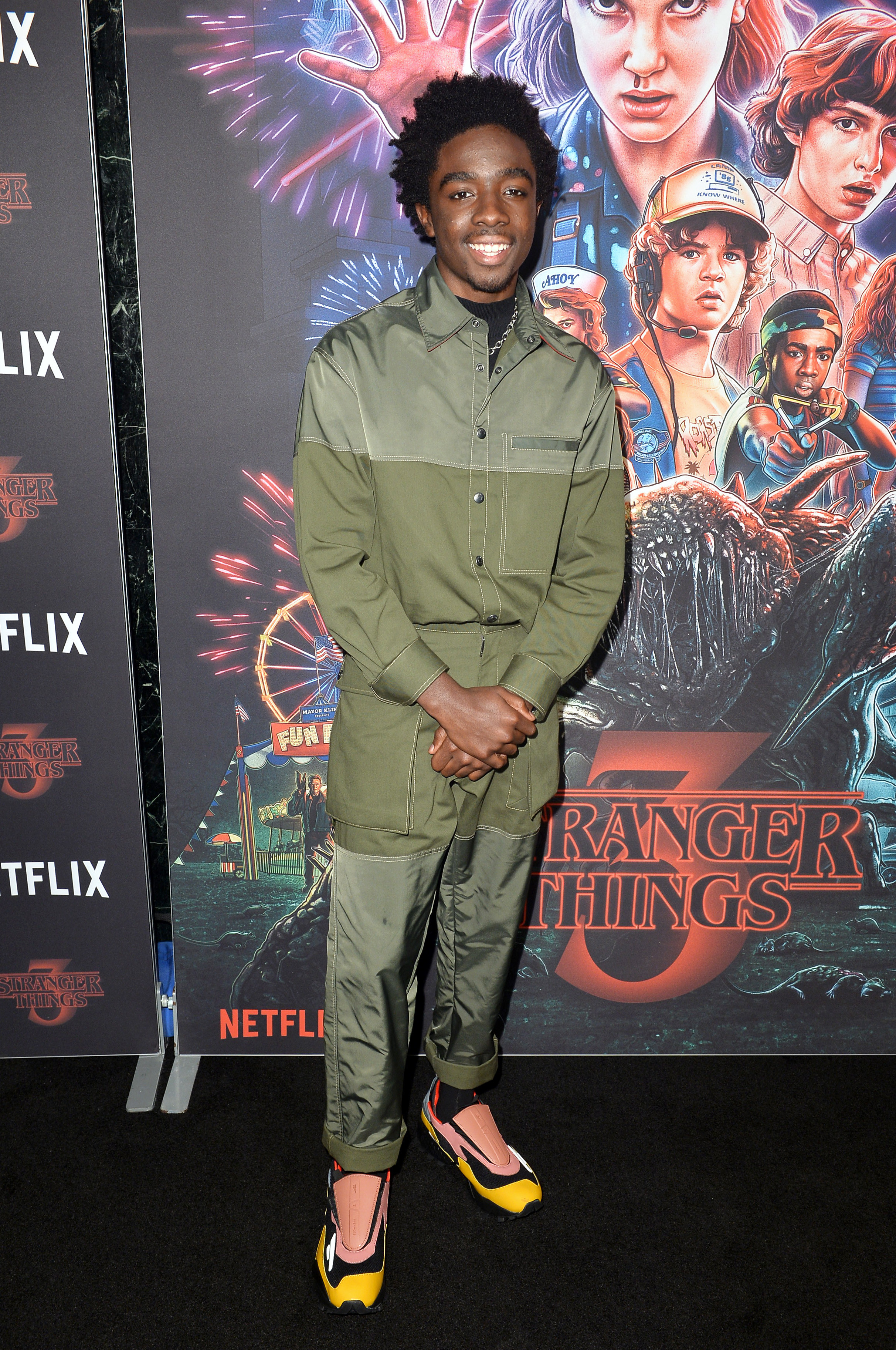 Caleb is smiling at a premiere wearing another monochromatic outfit with multicolored sneakers.
