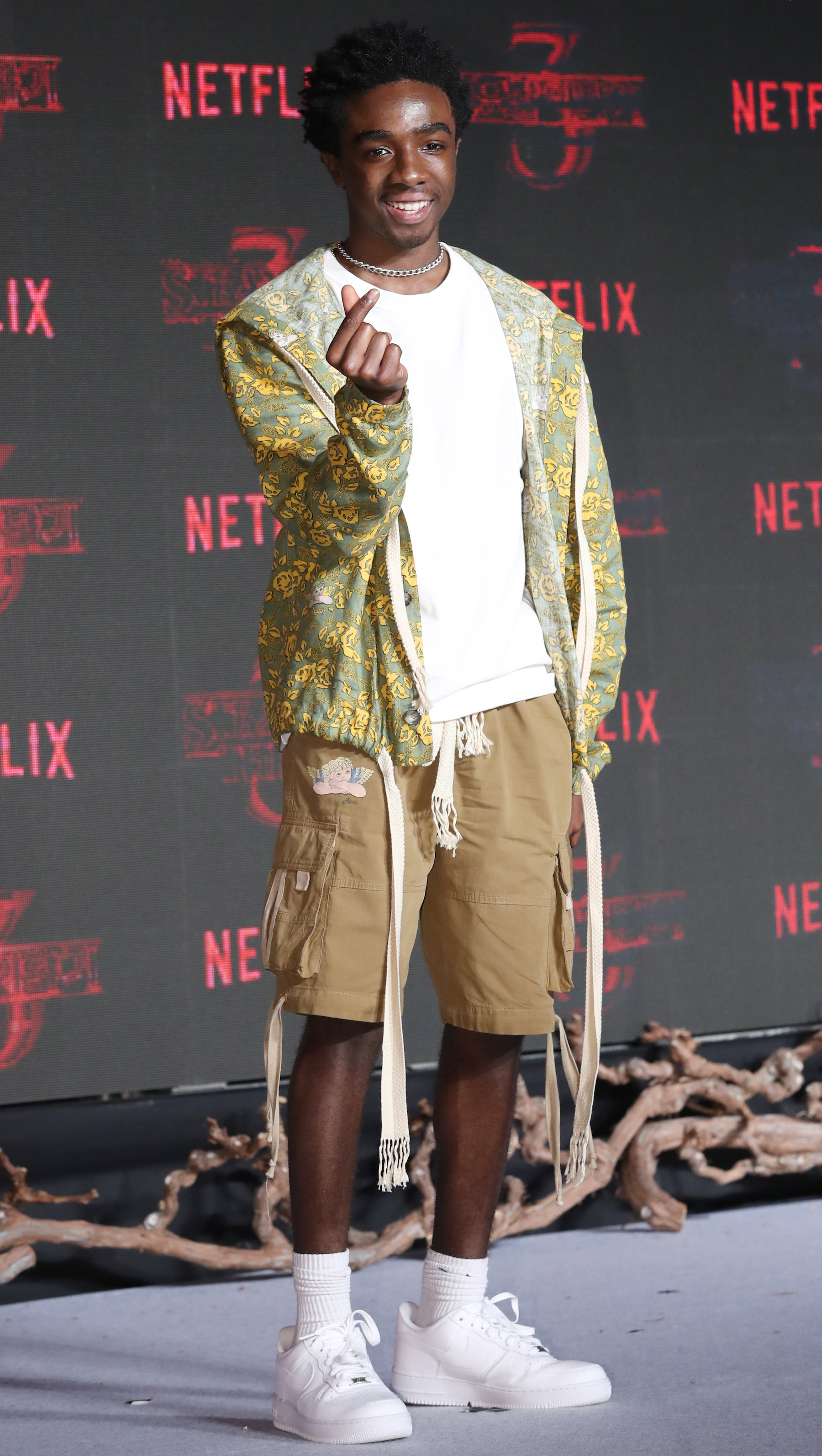 Caleb is at a premiere wearing a zip-up hoodie, t-shirt, and cargo shorts.