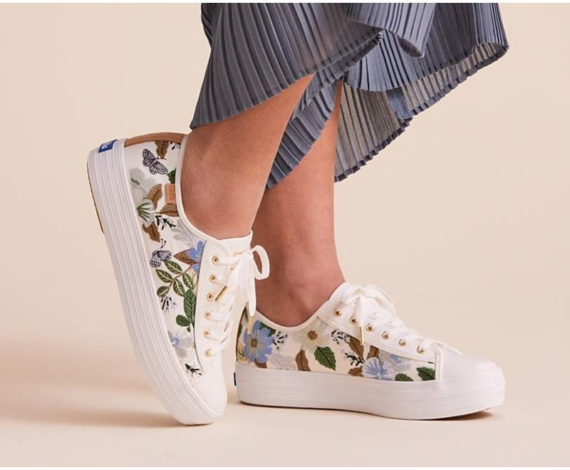 white sneakers with blue flowers and butterflies on them