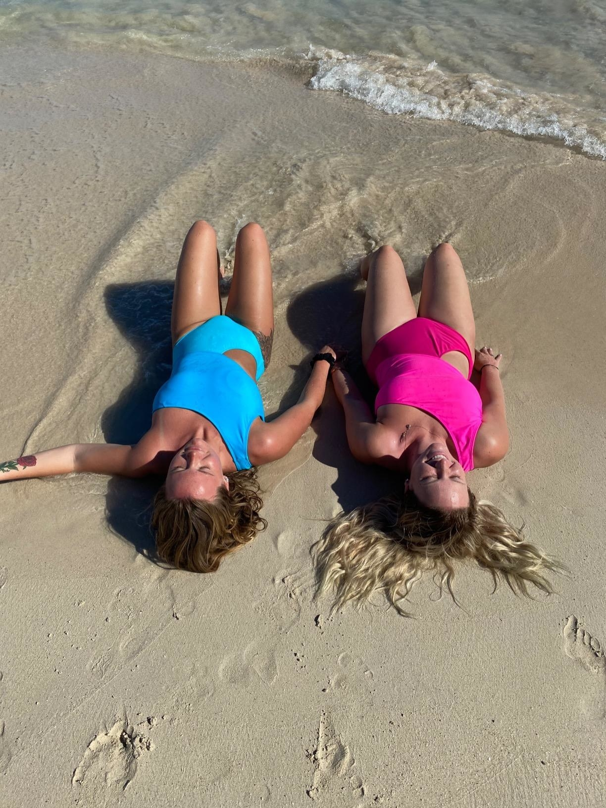 Two reviewers in the swimsuits: one in two tone pink and one in two tone blue