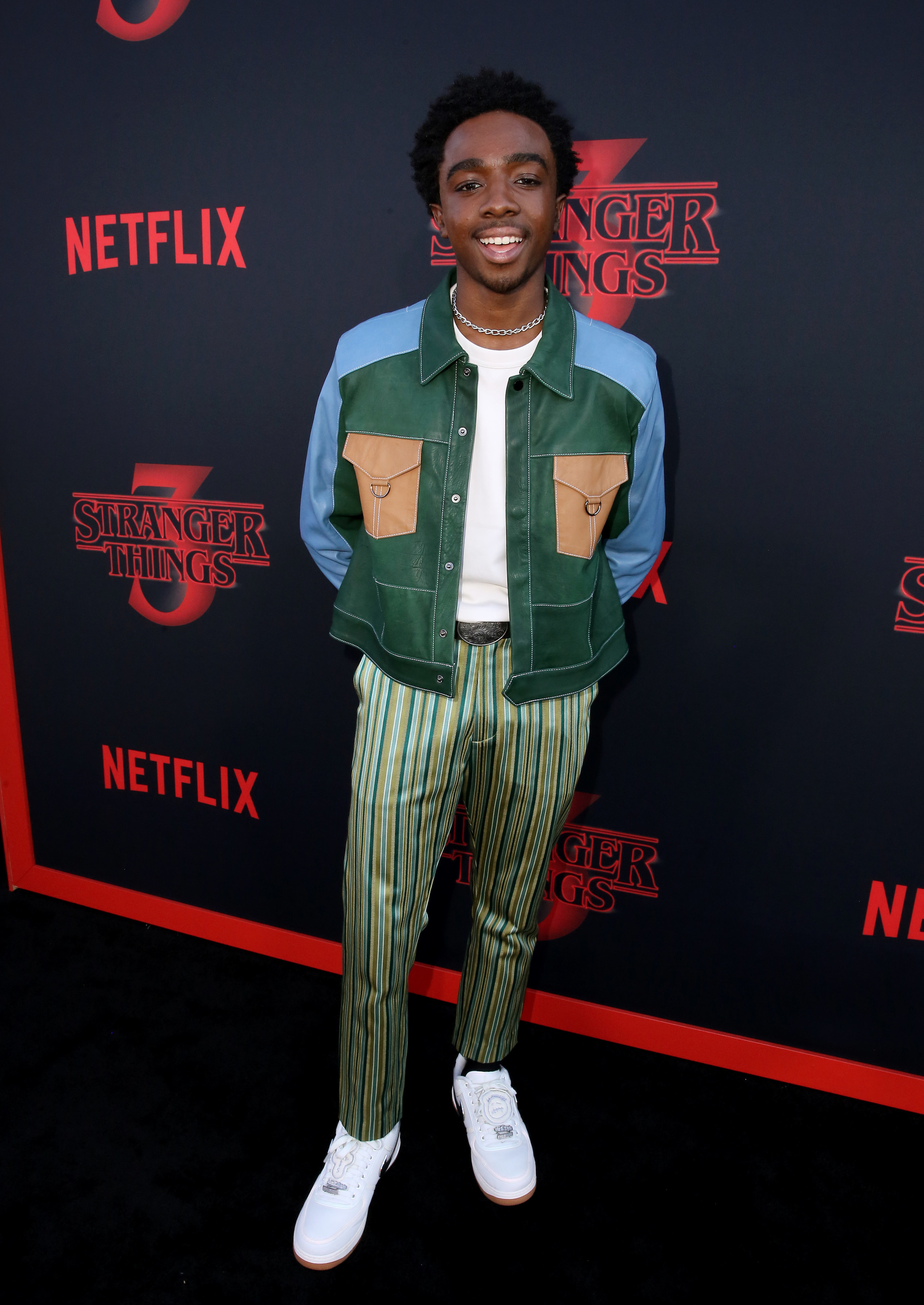 Caleb is smiling at a premiere wearing a multicolored jacket and printed pants.