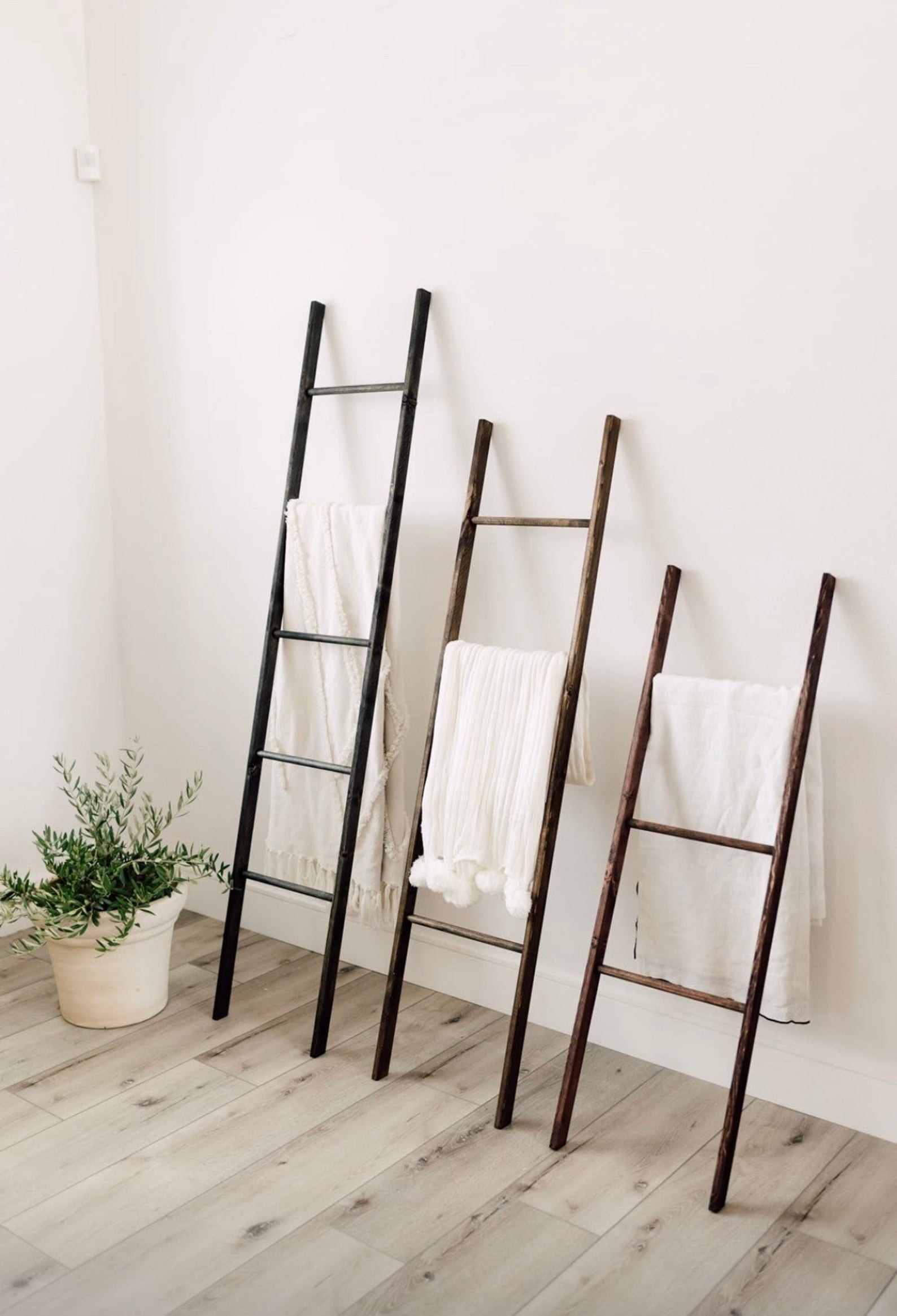 three blanket ladders of different heights lean against a wall, each with a blanket hanging from a rung