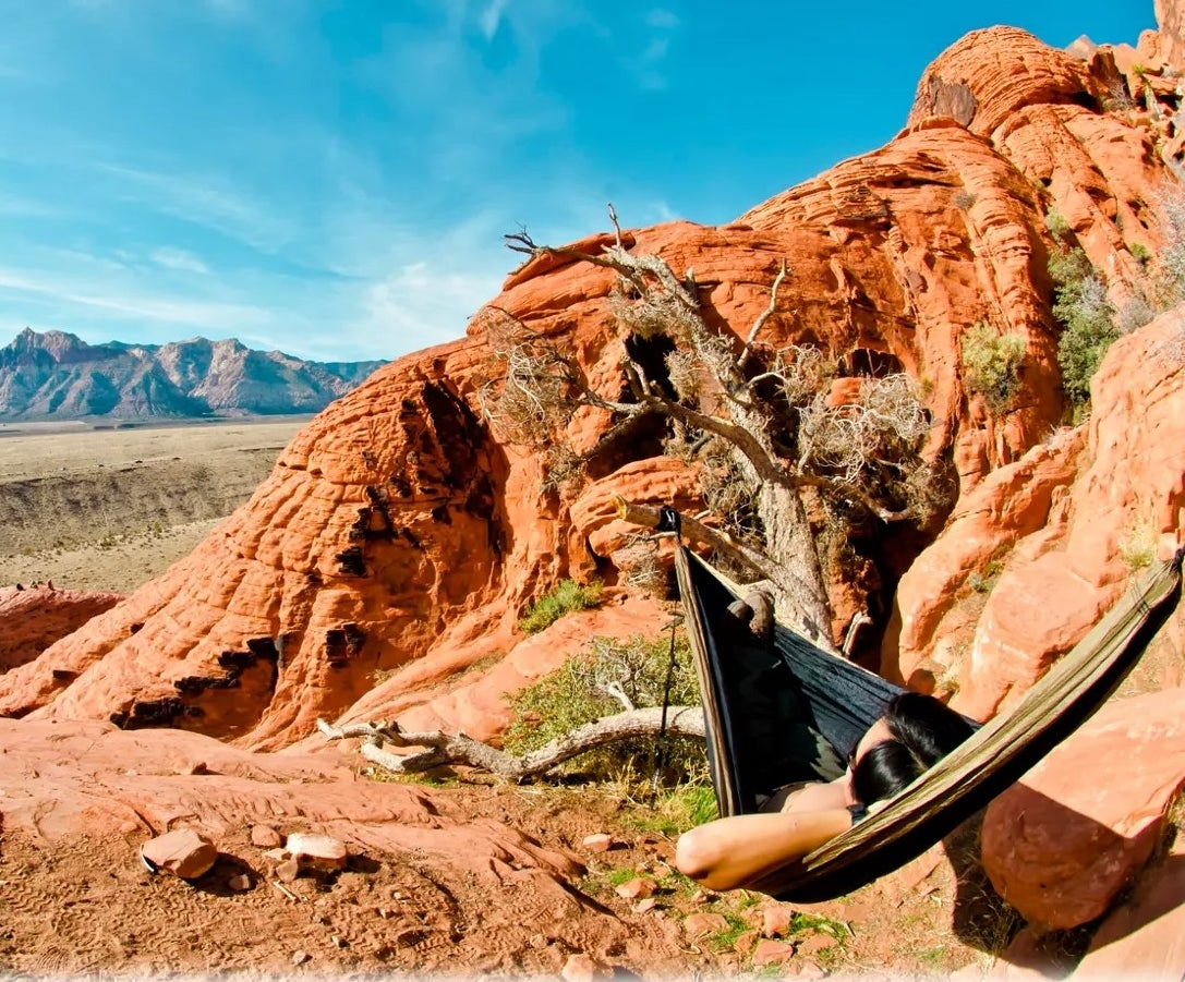 a person lougning on a hammock with a scenic view