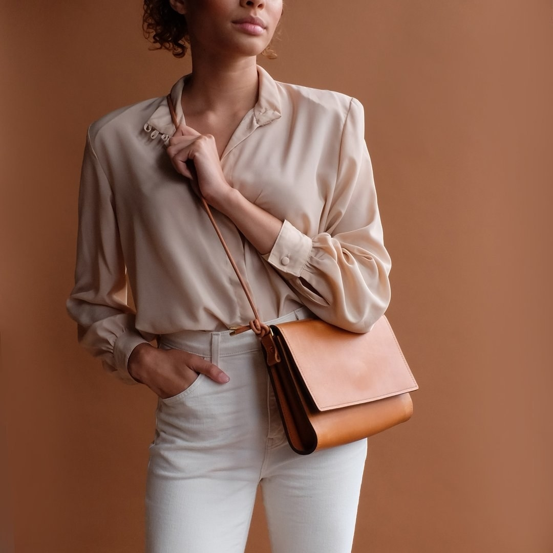 Model wearing tan crossbody bag