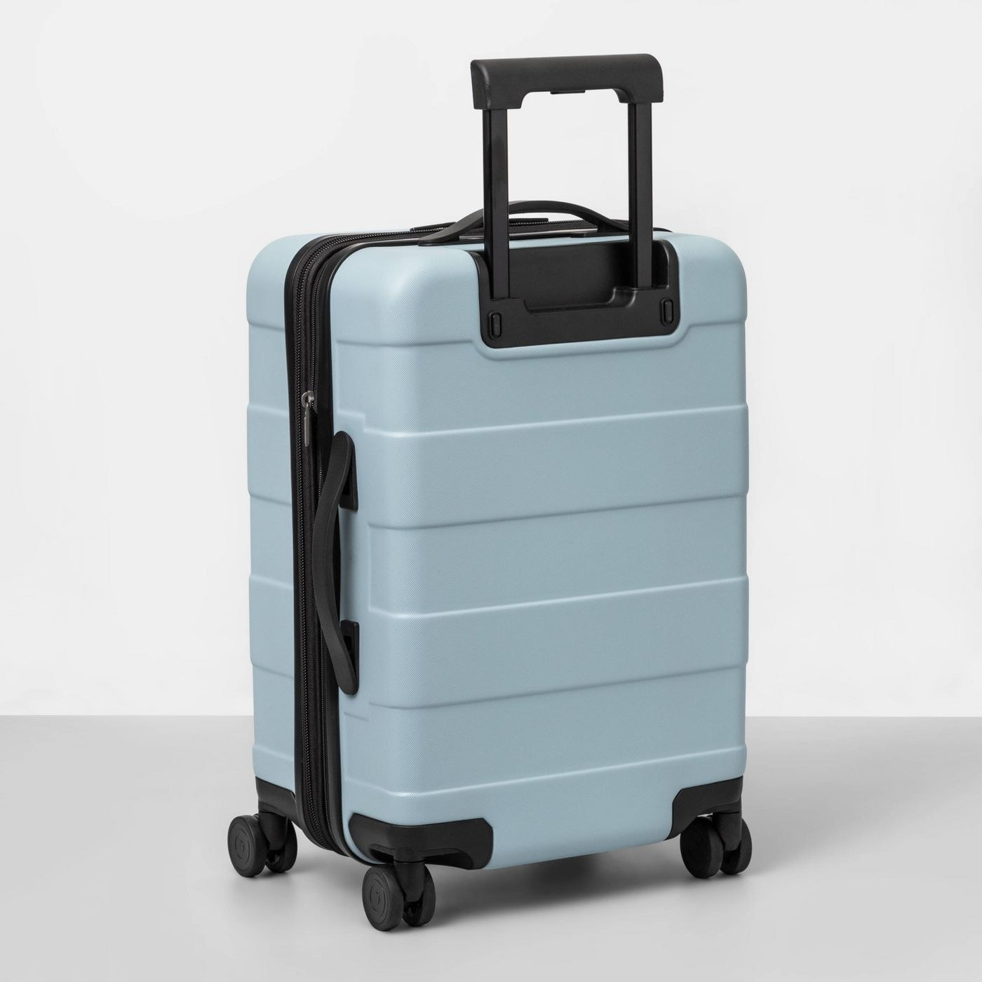 A light blue hard cover carry on suitcase
