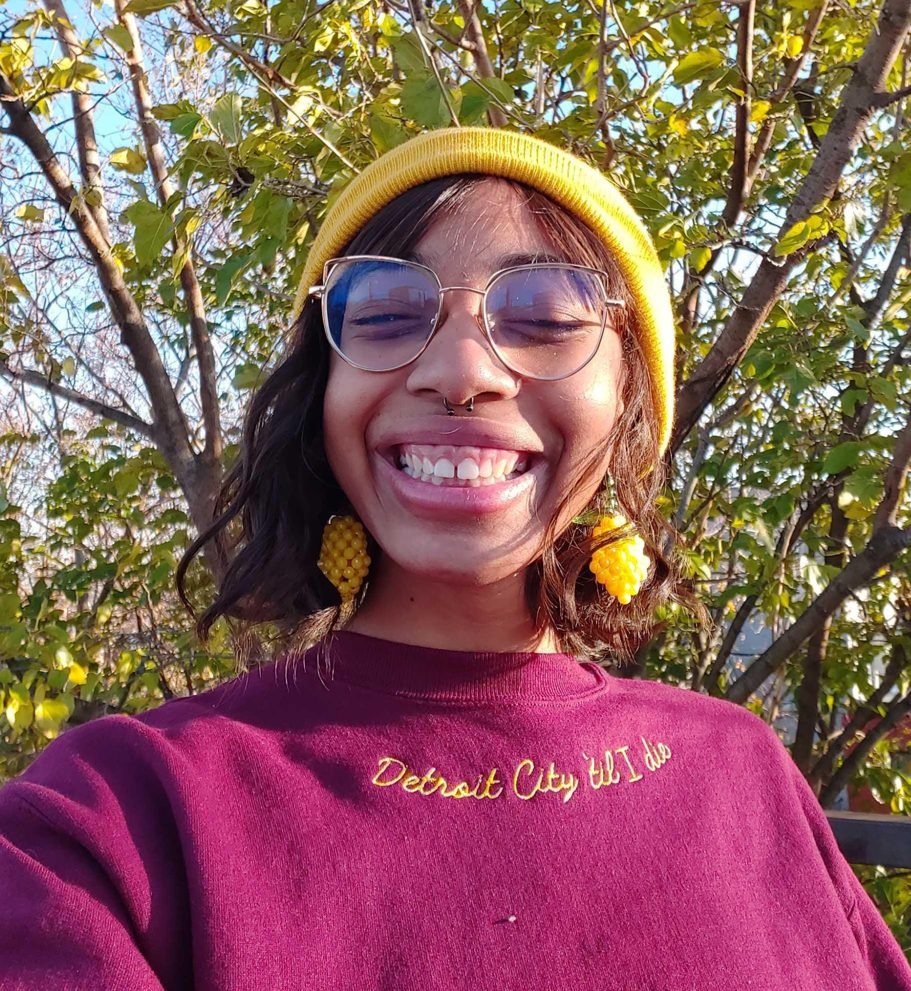 "buzzfeeder in a maroon crewneck sweatshirt with ""detroit city 'til I die"" embroidered in mustard along the neckline"