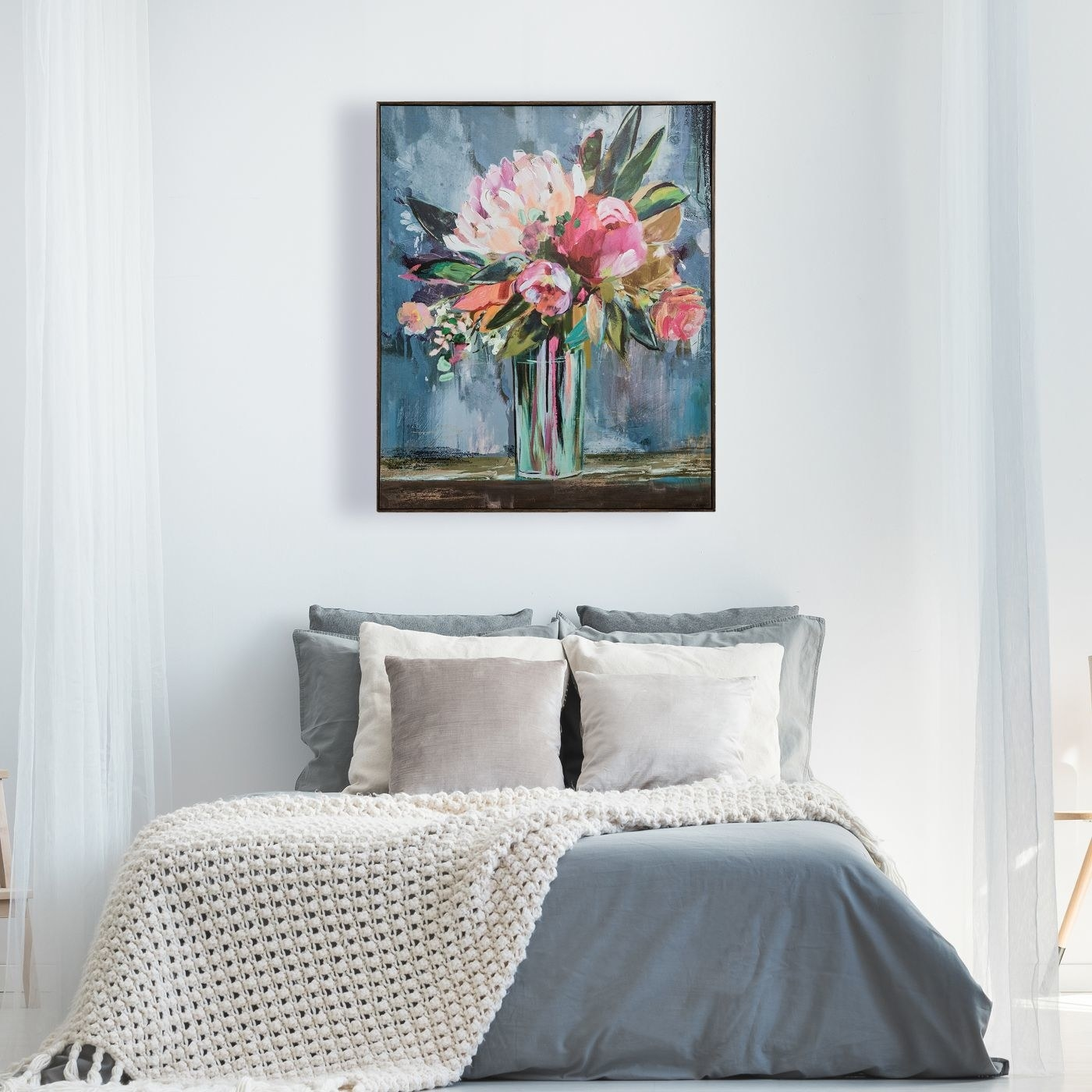 A floral framed wall canvas above a bed
