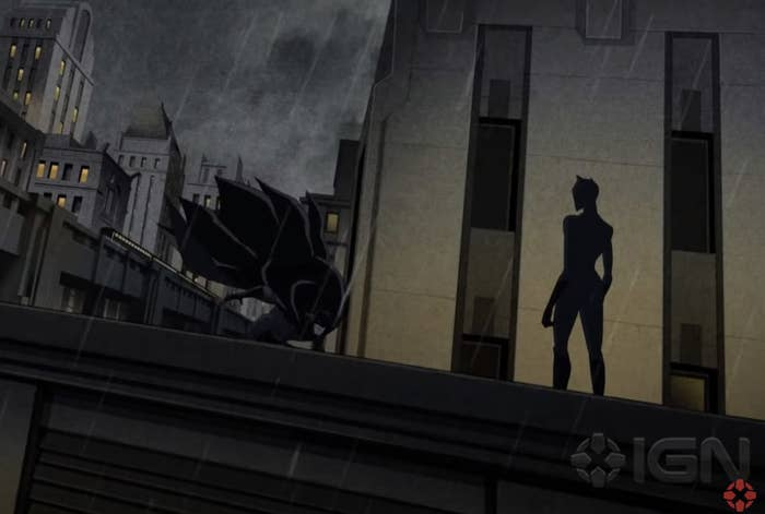Catwoman stands on top of a building with Batman