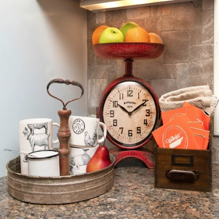 The tray with mugs stacked on top on a counter with fruit and coffee