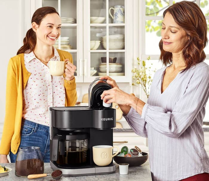Two women in a kitchen around a Keurig coffee maker