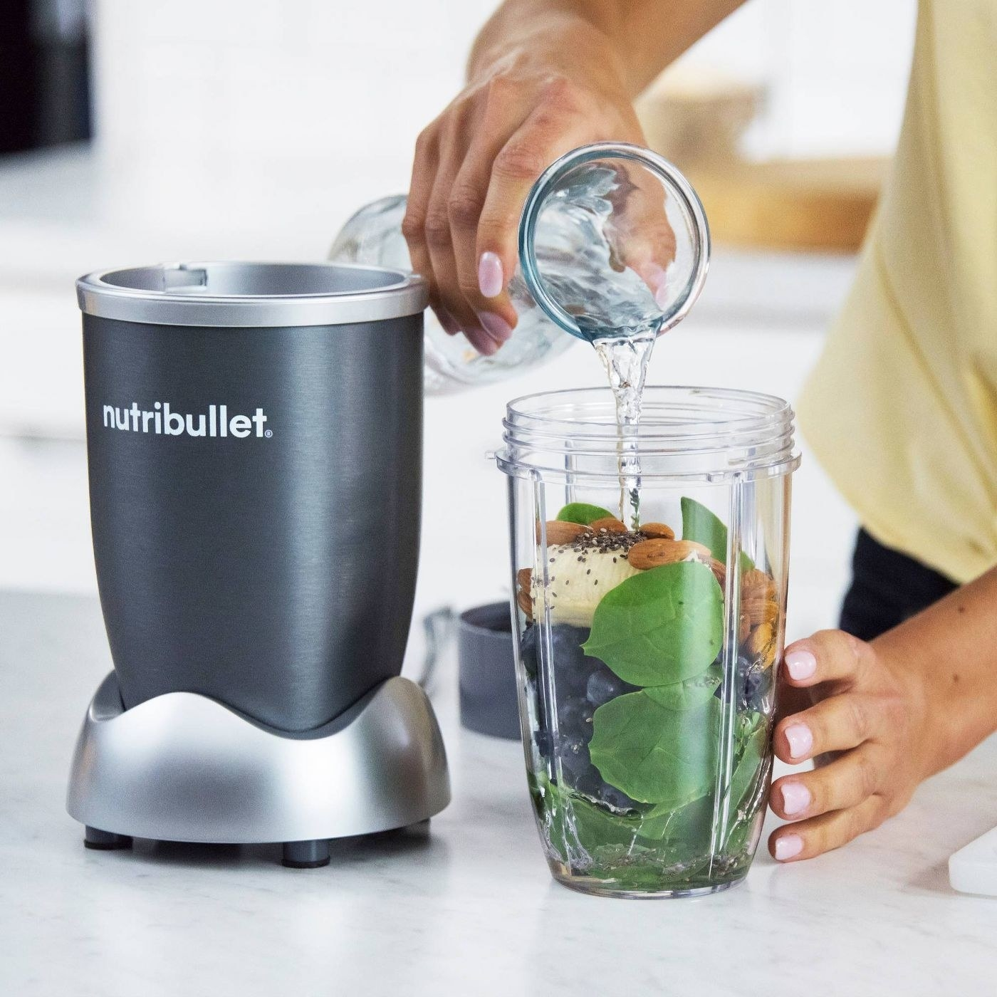 A woman making a smoothing with a NutriBullet blender