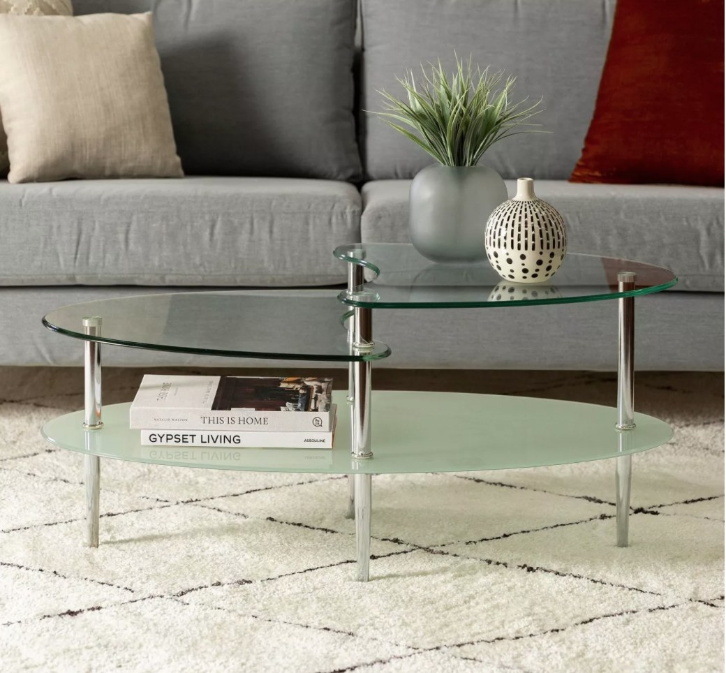 The coffee table with a plant on top and books on the lower shelf