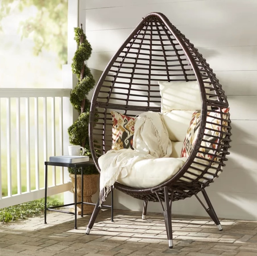 Brown wicker tear-drop shaped chair with white cushion