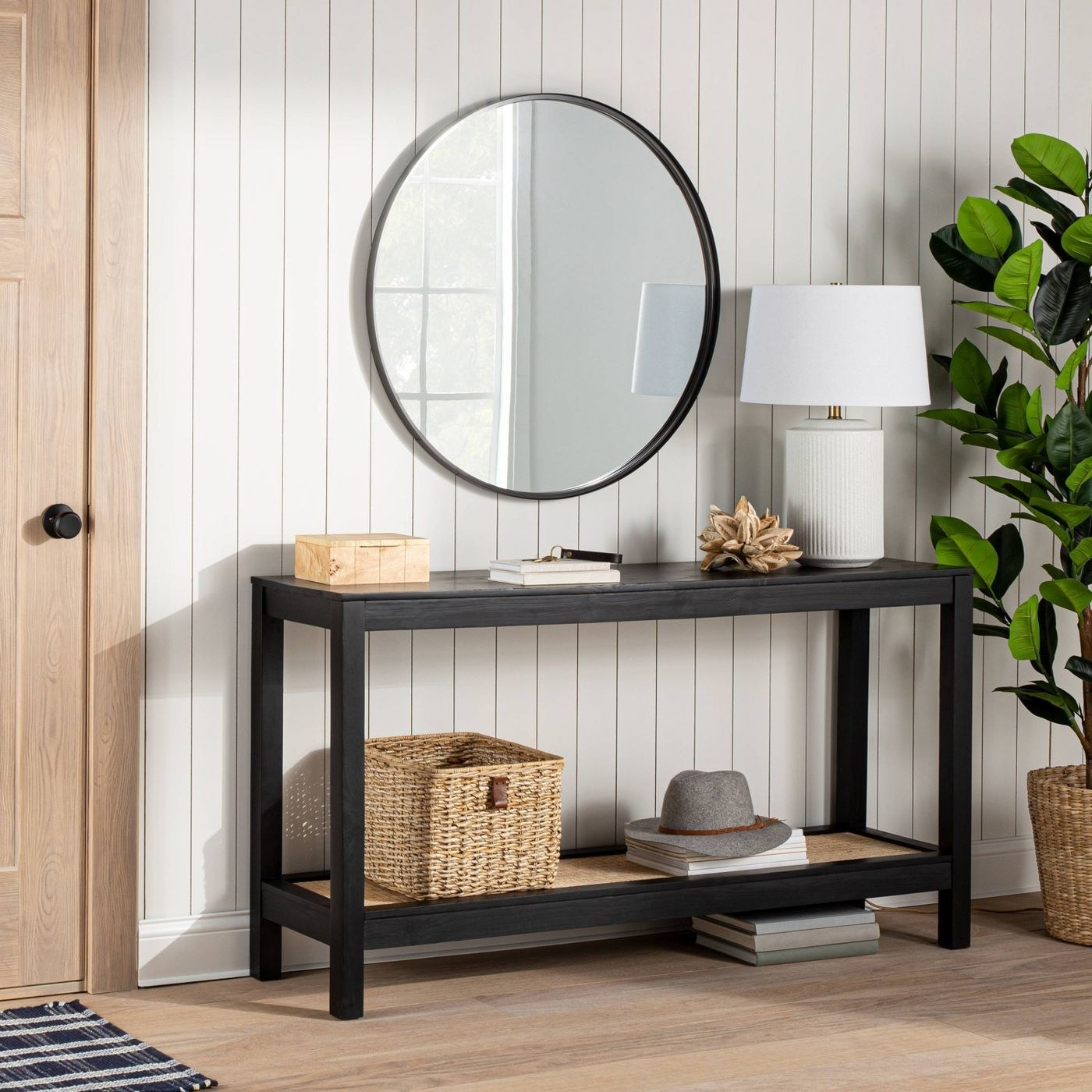 A round mirror above a console table in an entryway