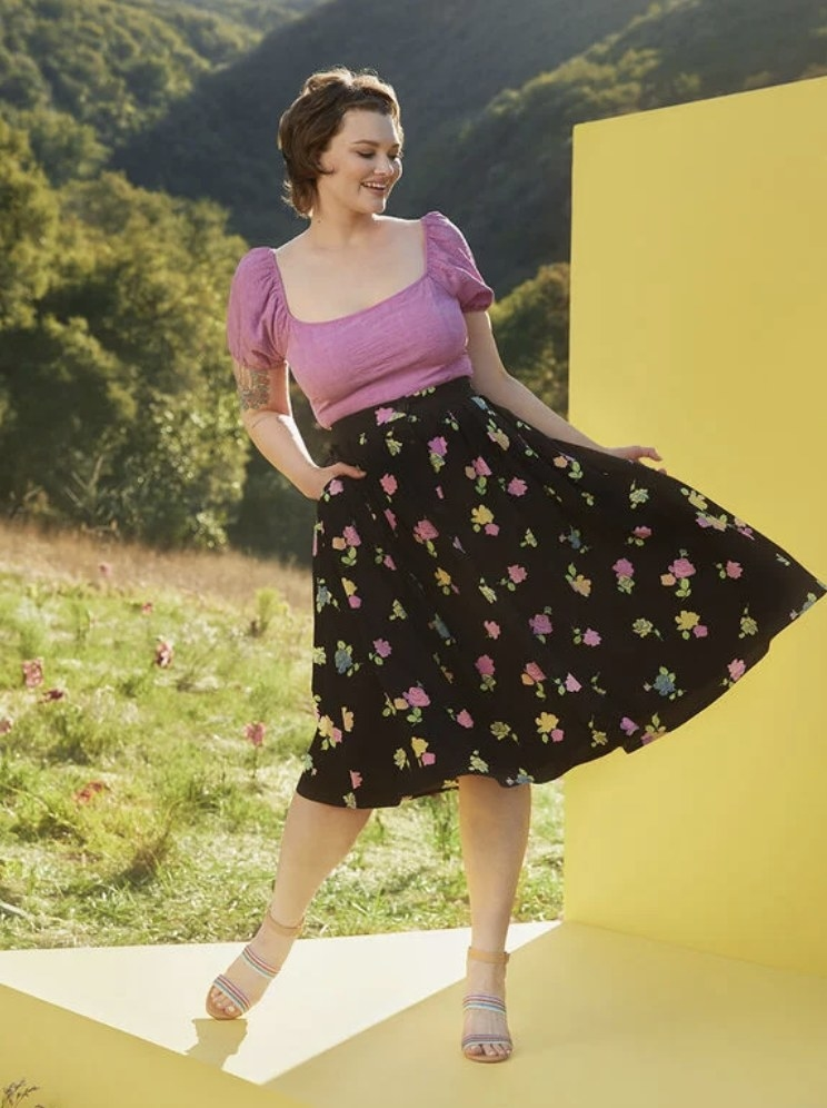the skirt on a model in floral print with sandals and a pink puff sleeve top