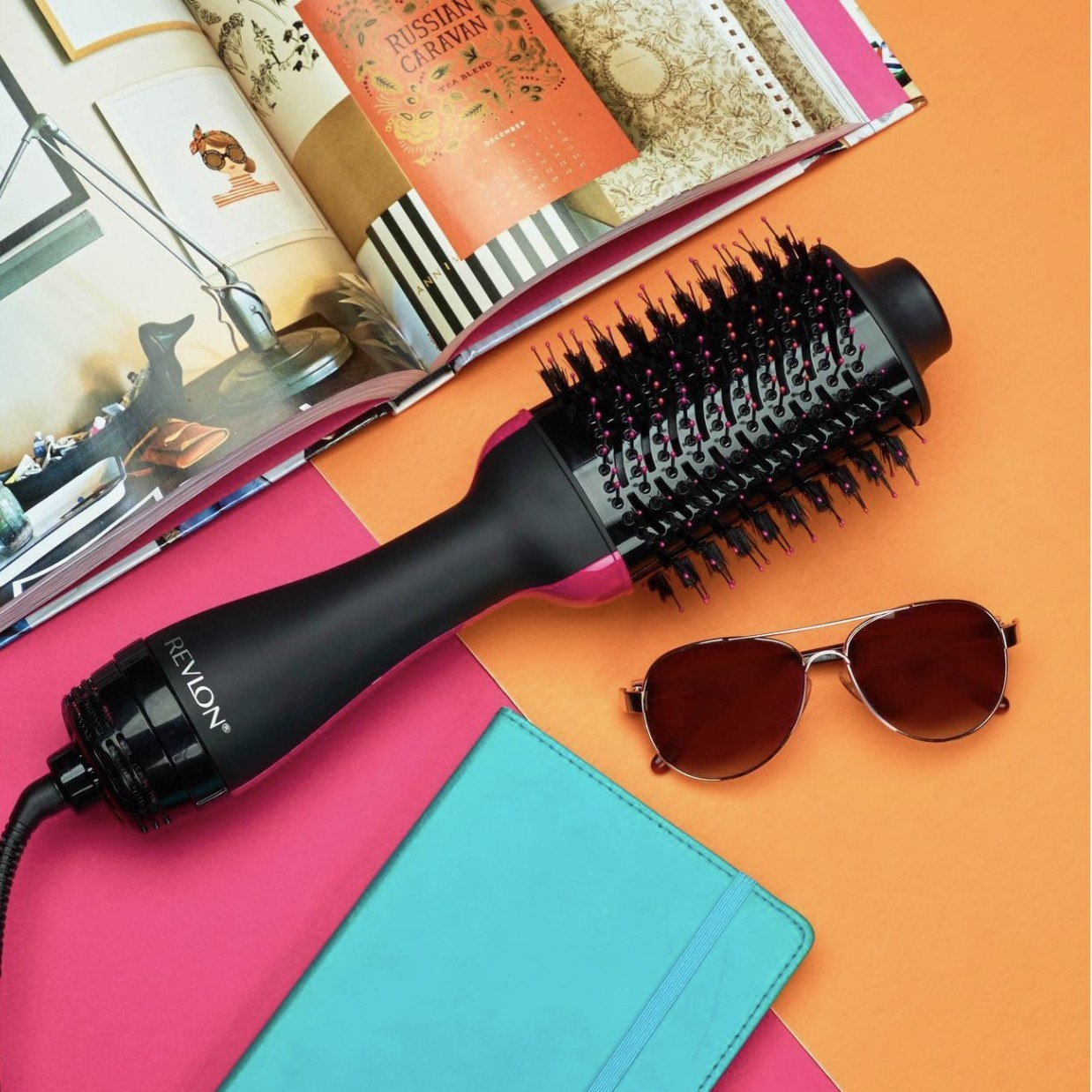 An electric round blow dryer hair brush on a colorful backdrop next to a notebook and sunglasses