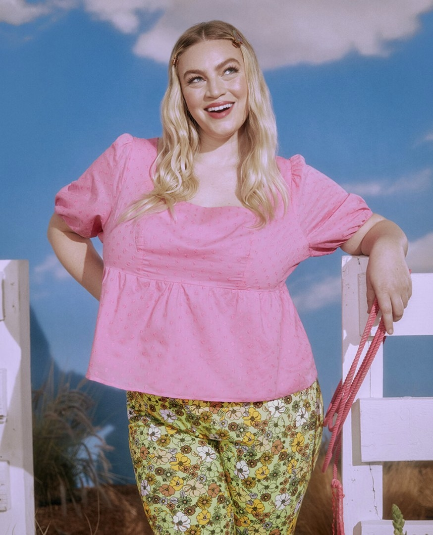 the top in pink on a model with floral print pants