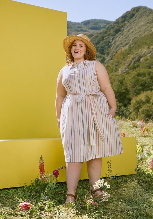 the dress in rainbow stripes on a model with a hat and brown sandals