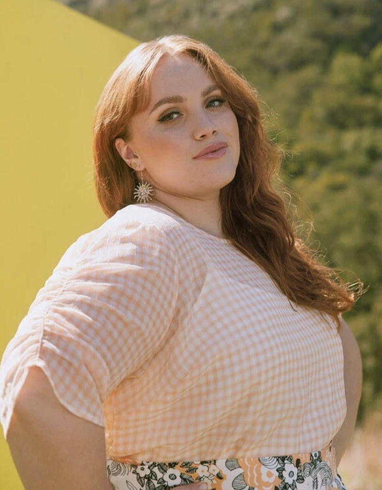 a model wearing the blouse in orange gingham