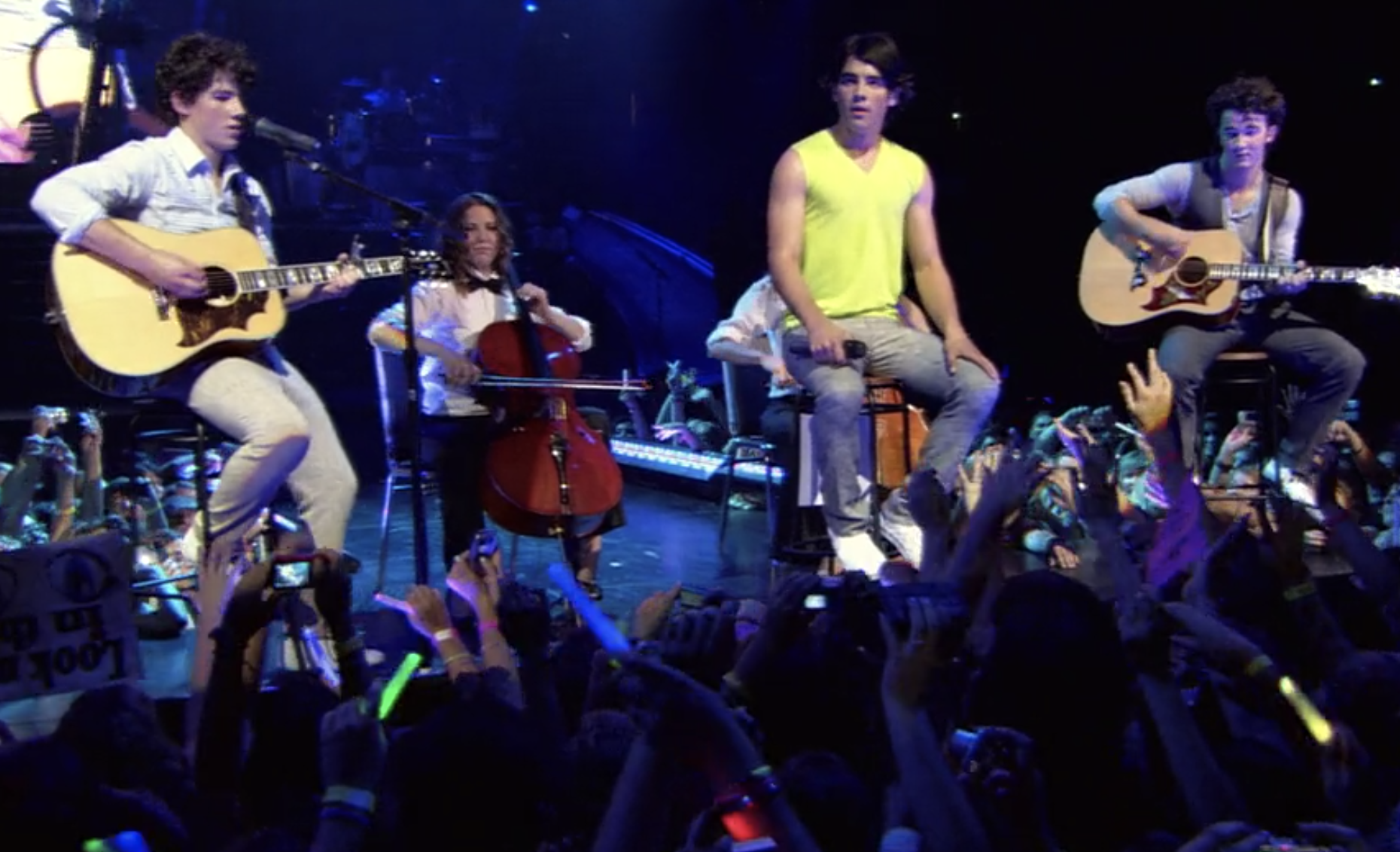 The Jonas Brothers sit down to perform a song as the crowd cheers them on