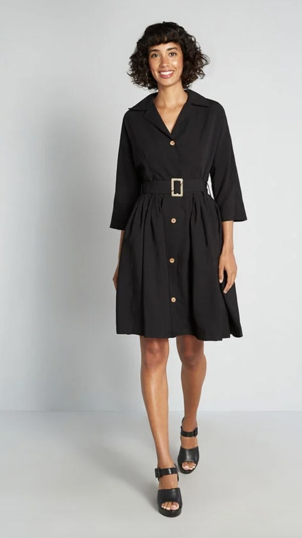 a model wearing the dress in black with black sandals