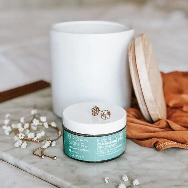 Urban Skin RX Event Tone Cleansing Bar on a vanity with earrings on top of it
