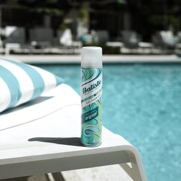 Bottle of Batiste dry shampoo on a pool chair with pool water in background