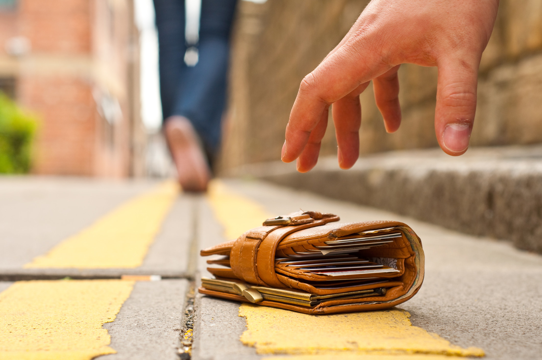 Thief picking up a lost wallet off the street