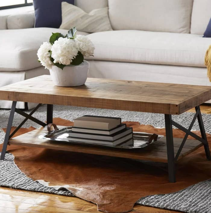 The coffee table with storage in natural pine brown holding a tray of books and flowers