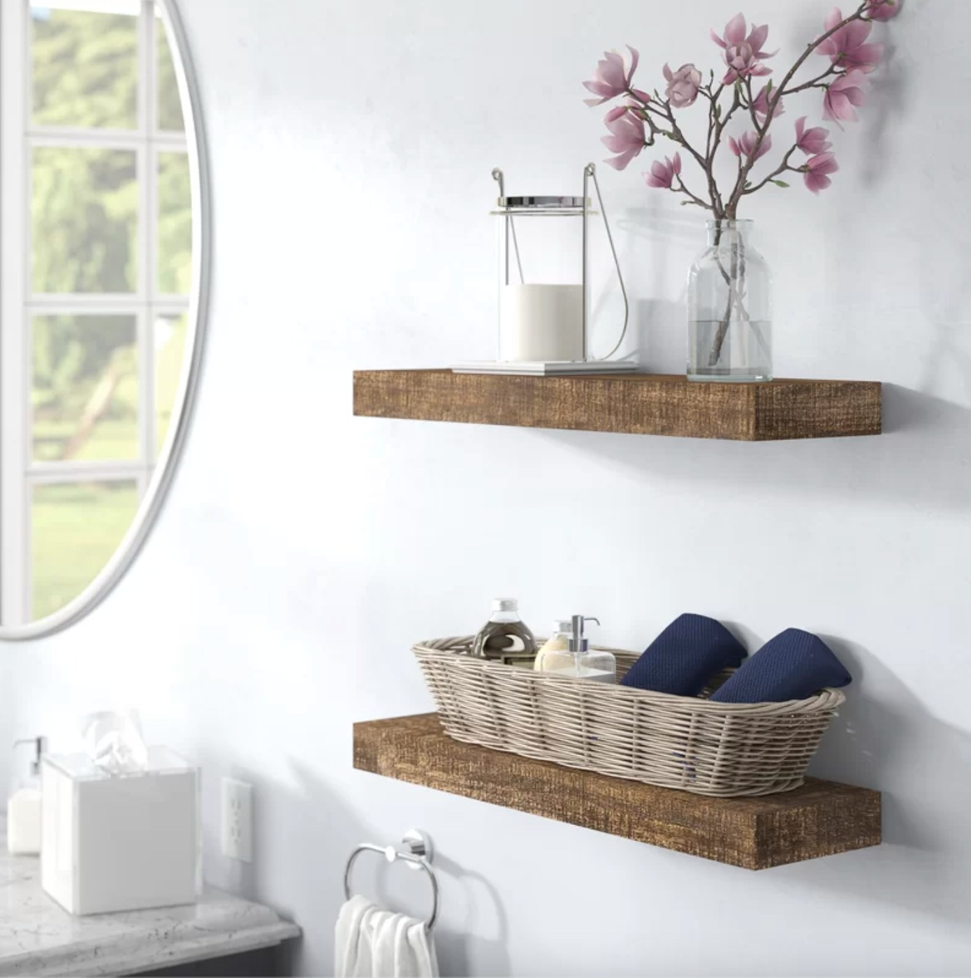 The two-piece set of solid wood floating shelves in dark walnut holding towels, candles, and a vase of flowers