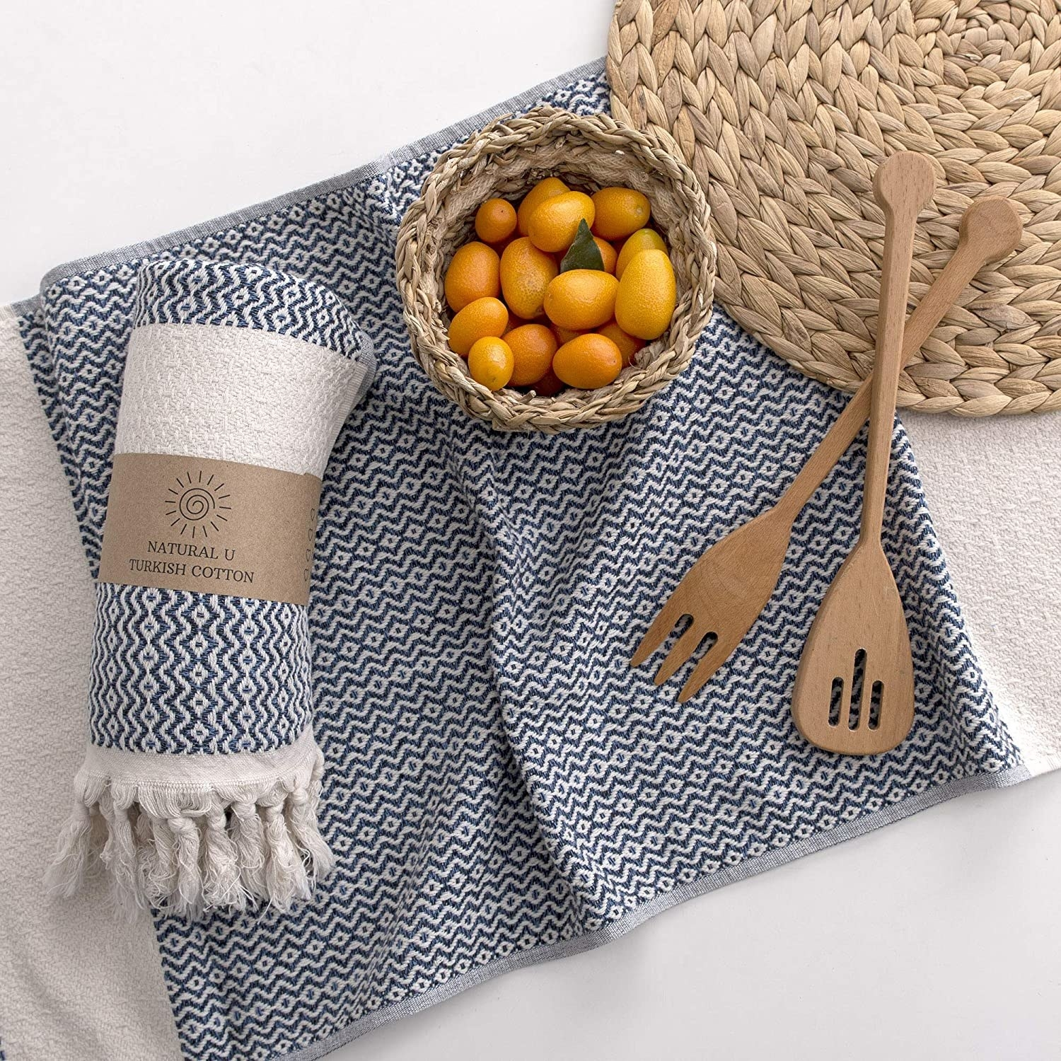 A flatlay of the turkish towels next to a bowl of citrus and some kitchen utensils
