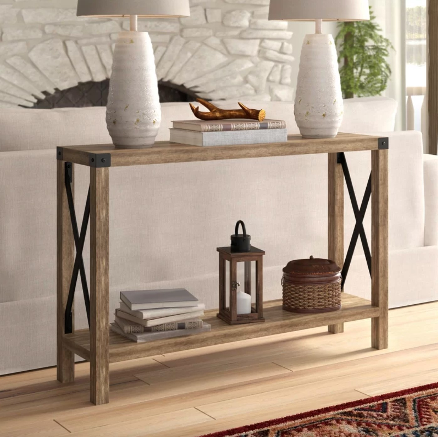 The wood console table holding books, lamps, and trinkets