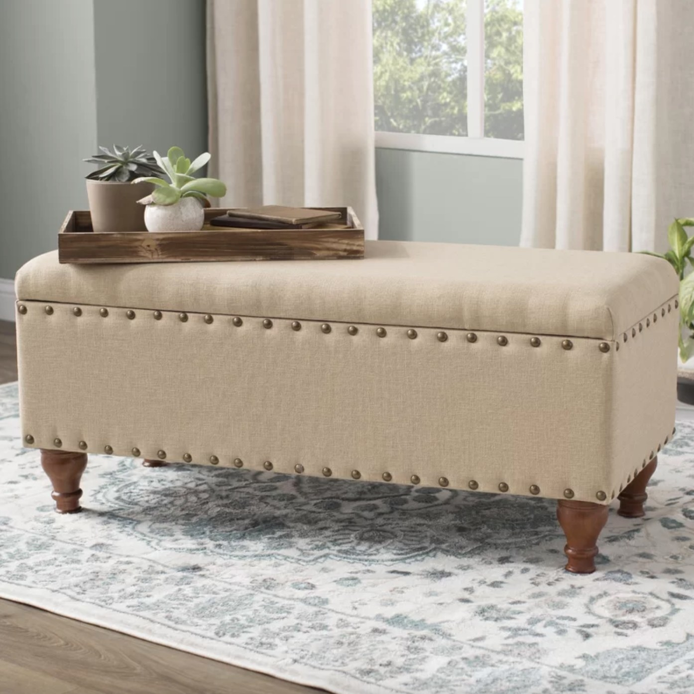 The flip-top storage bench in tan with brushed brass nailheads