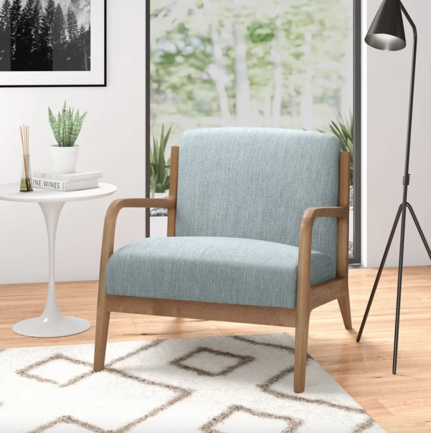 The wide armchair in light blue with a light wood frame