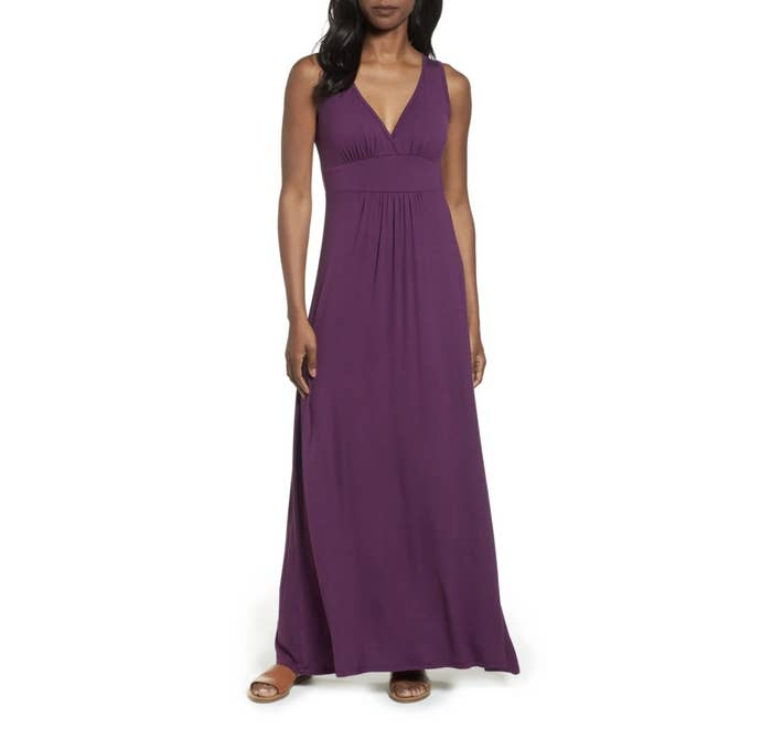 Model is wearing a purple maxi dress and sandals