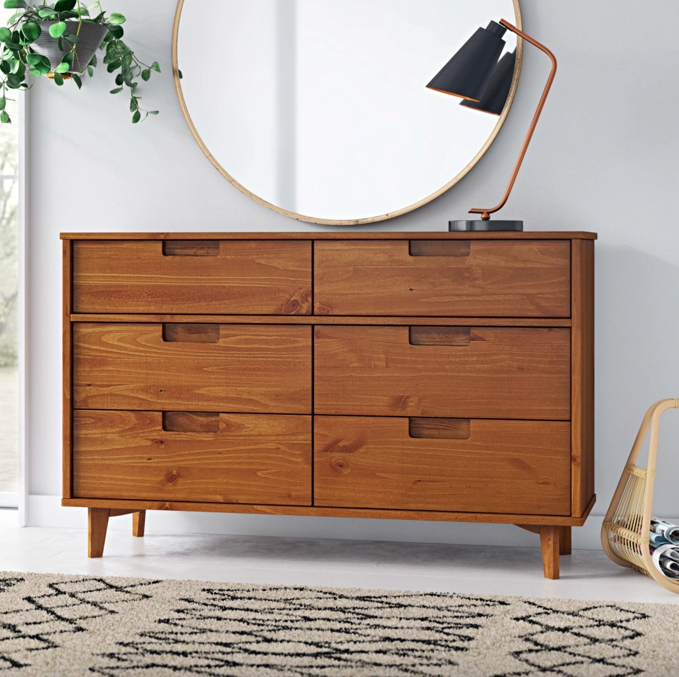 The six drawer double dresser in caramel with a large round mirror hanging above it