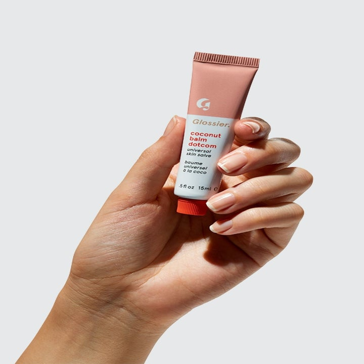 hand holding a tube of the coconut balm