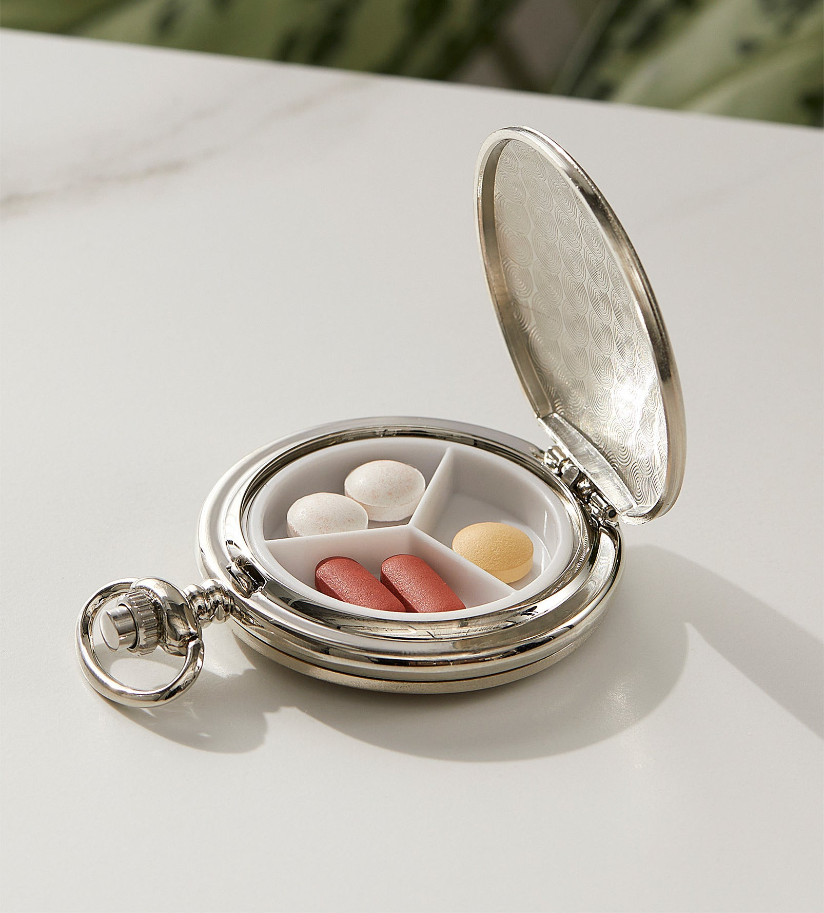 A pocket watch-shaped pill case open on a counter to show off the inner compartments