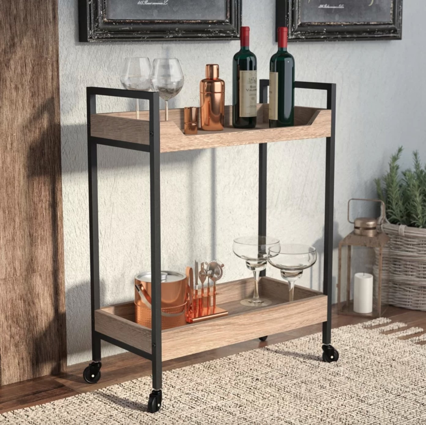 The bar cart in charter oak holding glasses, wine bottles, and cocktail kits