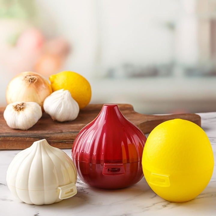The closed containers, which are shaped like garlic, onion, and lemon